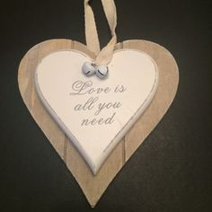 Wooden hanging plaque with double hearts, message 'Love is all you need' & adorned with two jingle bells. Add to your wedding venue to celebrate your love for each other.