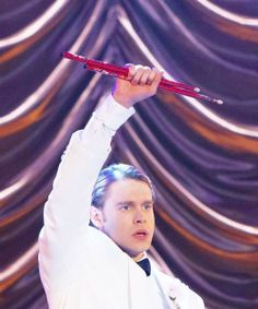 Sam holding Finn's drumsticks aloft, Nationals 2014