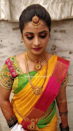 Bridal perfection! Sowmya looks colourfully gorgeous for her muhurtham. Hair and makeup by Team Swank. South Indian bride. Bridal silk saree. Saree blouse design. Smokey eye. Pink lips. Maang tikka. Bridal gold jewellery. Jhumkis.