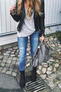 a girl wearing combat boots ripped blue jeans a grey tshirt and leather jacket