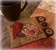 Love Rug is a folk art mug rug with three wool penny tabs embellished with buttons. The cute little rug can also be used as a candle mat. It features underlaid vintage lace that adds texture and romantic charm. This cute and whimsical rug would make a great gift for a teacher, coffee
