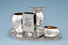 A silver Fabergé desk set, Moscow, 1892. An ovoid tray with two removable bowls, a candle holder and a matchbox holder, all engraved with the initials 'AT'.