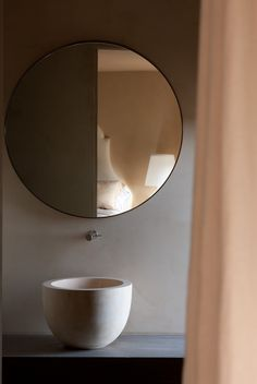 Powder room - of note: round mirror with steel frame, wall mounted faucet, vessel sink.