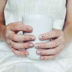 Nude nails with a black dot at the base.