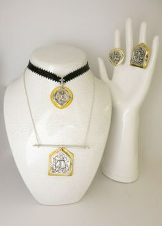 """Amuletic necklaces and rings with ancient """"deity"""" die-stamp embossing in sterling silver with gold plated brass detailing."""