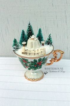 A Christmas Tea Cup Fairy Garden with a tiny fairy tea setting for two!  Handcrafted from polymer clay and painted with fine details, the tea set