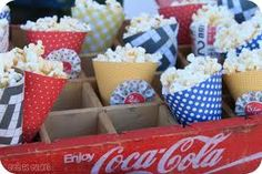 Paper cones hold popcorn.  Some have handmade paper rosettes.  Would be really cute with a homemade snack mix inside.
