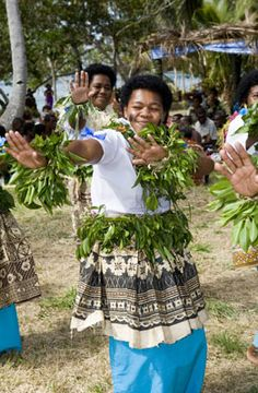 Yavusa women dance in traditional dress at the opening ceremony. Though Fiji is modernizing rapidly, many residents of outlying islands like Mali still live in huts with no electricity or indoor plumbing. [Source: National Geographic]