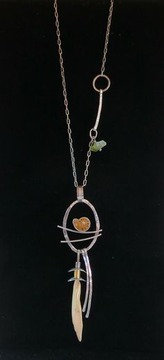 Elaine Rader Jewelry Galleries  ||  Fossil mammoth ivory and ammonite pendant with peridot bead.  $365.00