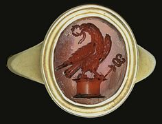 A ROMAN CARNELIAN RINGSTONE   CIRCA 1ST-2ND CENTURY A.D.   The flat oval stone engraved with an eagle standing upon an altar, its head turned back, a laurel wreath in its beak, a caduceus to the right; mounted as a ring in a modern gold setting