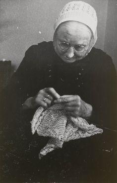 Vrouw in Cadzandse streekdracht. De vrouw is gekleed in daagse dracht en is aan het handwerken.
