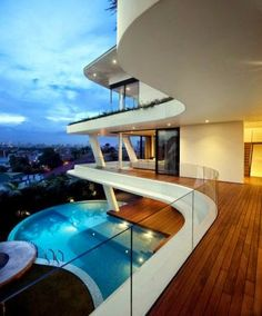 nice curved glass panel railing. love the wood decking and white stucco.