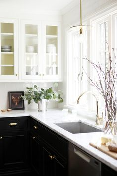 Black lower kitchen cabinets, with marble counter tops and white upper cabinets | Katie Hackworth