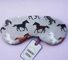 Eye Sleep Mask, Brown, Grey, Black & White Horses by Diamond Desola  -Sleep mask printed with horses on dove grey background. (exact positions and colours of horses will vary according to fabric) -Light flexible padded layer. -Plain black all cotton sateen on reverse. -Black corded elastic to keep mask in place while in use. -Measures approx 18cm across <------- > -Diamond Desola - Hang Tag and Satin Ribbon, on card and in a protective cellophane pack - ready to give as a gift. -Th...
