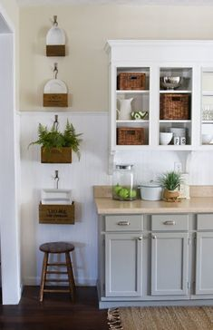 White bead board back splash, two toned kitchen cabinets grey bottom, white upper, wood floors, hanging wood crates