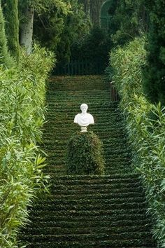This long stairway covered in greenery is definitely one-of-a-kind! A white marble bust stands alone on the landing, while in the distance we spy a magnificent home.