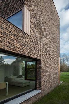 Bakstenen contrasteren met de strakke vorm van de woning.