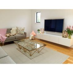 Contemporary Scandinavian decor, copper coffee table, floating TV unit, low pile woven rug, London couches, pastel colours.