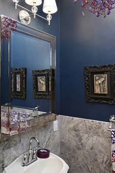 A small power room is the perfect place for creating drama. Nirmada chose a dark blue wall color for this small room, while travertine tiles cover the floor and walls adding texture. A purple chandelier is the element of sparkle.  more