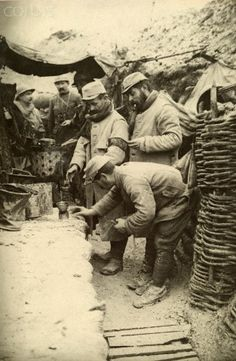 French WWI soldiers in a front line trench warm some wine. - 42-32919432 - Rights Managed - Stock Photo - Corbis