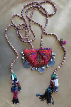 Kinship Stories: Indian Hindu rosary base. Vintage Afghani centerpiece, hand-embroidered. Ottoman coins (over 150 years old) and vintage mixed silver beads from Yemen. Old Uzbek tassels and charms from India, Nepal and Turkey. This necklace is entirely handmade and a unique item.