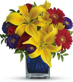 Teleflora's Blue Caribbean yellow lilies and colorful flowers in a blue glass cube vase