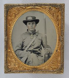 Ambrotype of Georgia soldier with SHG (Stephens Home Guards) on his hat. He holds a musket and also has a visible canteen and Bowie knife.