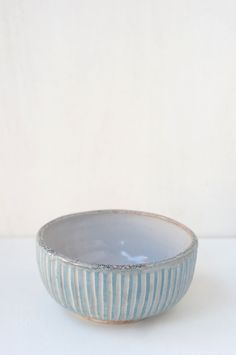 A small bowl with hand-carved pale blue and white stripes on the exterior, and a freckled rim. The inside is glazed white. A good size for a petite breakfast or