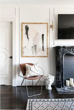 simple art in modern living room via sfgirlbybay | white panelled walls | retro leather and metal armchair with a mudcloth cushion | patterned rug and dark wooden floors | elegant marble fireplace |
