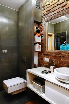 W ściance skrywającej instalację podwieszonego sedesu i przewody kominowe zrobiono wnękę z półeczkami. To dodatkowe miejsce na przechowywanie, którego w tej łazience nie ma zbyt wiele.
