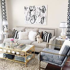 playful and posh, this luxe glam style living room interior design features a leopard print rug and grey blue velvet upholstered chair