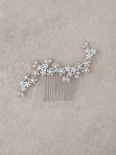 Esta peineta de novia, de gusto delicado, muestra un diseño de flores elaboradas en plata vieja y pedrería, para cononar el mejor de los recogidos