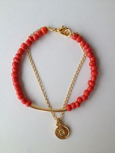 red beaded bracelet with gold tube and crown pendant Pulseira vermelha