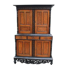 British colonial cabinet, detailing including solid, carved apron, upper section with two cupboard doors enclosing two stationary shelves, lower section with three drawers above two cupboard doors enclosing one stationary shelf.