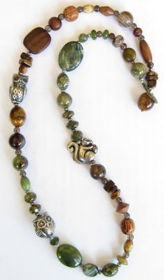 """If your beads were just too darn cute to pass up (like the ones from Green Girl Studios used in our necklace pictured at right), think about what kind of """"environment"""" your beads could live in. We envisioned our pewter squirrel & owls living in a forest, so we chose a palette of browns & greens. We made a point to balance the pewter critters with slightly larger beads, so our odd-ball orphan gemstone & wood beads worked well."""