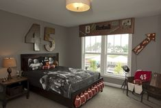 Football themed boy's room features hammered metal jersey number mounted over wood bed adorned with row of footballs on footboard dressed in football themed bedding flanked by single nightstand topped with table lamp and vintage fan.