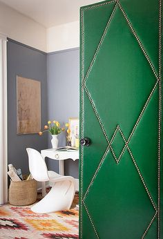 Another upholstered door to consider is the one spotted on Design*Sponge, that pairs a deep emerald green vinyl with nail-head trim to create one serious show-stopper. - The colors, the pattern rug, the mix of furniture, everthing in this room is perfect!
