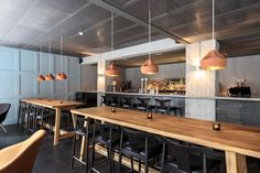 Nice industrial look. The wood tables soften the concrete and metal that makes up most of the room. I would hazard to guess that the construction was affordable too!