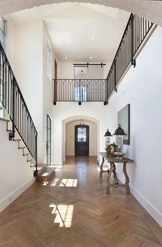 Transitional French Entry design with a touch of country French with the barn doors upstairs and the simple metal railing design.