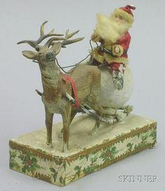Santa and Reindeer Candy Container, Germany, early 20th century, modeled as a tiny all-bisque Santa doll sitting on a snowball on travaois drawn by a metal reindeer, on rectangular box (missing box bottom), ht. 5 1/4 x lg. 5 x wd. 2 1/2 in.