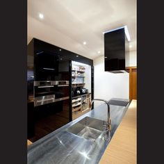 Opening the fully integrated pantry brings the wall of black acrylic to life.