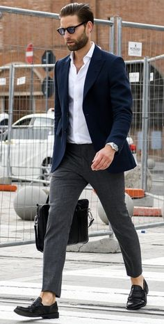 Smart casual outfit idea with a white button up shirt with a navy blazer gray trousers no show socks black penny loafers silver watch black leather messenger bag.
