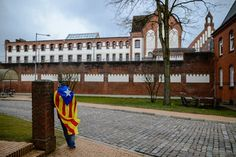 Neumünster, Germany A man wears a Catalan independence flag as he stands in front of the prison where Carles Puigdemont, the former Catalan leader, is detained