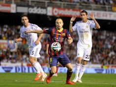 Andres Iniesta (C) of FC Barcelona gets past Angel Di Maria (R) and Daniel Carvajal of Real Madrid during the Copa del Rey Final between Real Madrid and Barcelona at Estadio Mestalla on April 16, 2014 in Valencia, Spain.