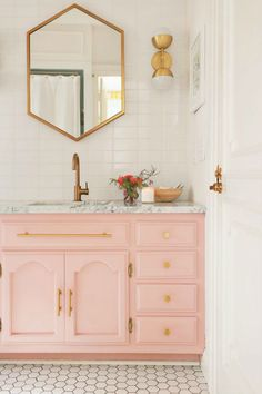 Banheiro com armário rose com mármore carcará e espelho hexagonal dourado