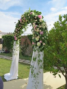 Arch with cloth and white dahlia, pale pink roses, pink peonies and greenery. Event Planner : Wedding Italy.