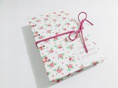 Agenda de bolsa artesanal com tema floral em rosa, totalmente confeccionada à mão. <br> <br>Resistente e prática. <br> <br>Formato de bolso, ótima para carregar na bolsa para eventuais anotações. <br> <br>Possui capa dura com tecido laminado, folhas em sulfite, guarda em papel color set e courinho para fechar. Costura copta em fio encerado. Com 100 folhas (200 páginas) de papel sulfite sem pauta gramatura. Primeira página personalizada. <br> <br>IMPORTANTE: SE DESEJAR NOME NA ETIQUETA DA…