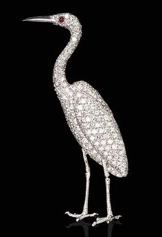 A DIAMOND EGRET BROOCH   The pavé-set diamond egret enhanced by a cabochon ruby eye, mounted in 18K white gold  The total weight of the diamonds is approximately 5.00 carats