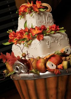 This unusual and whimsically stacked wedding cake captures the essence of fall with the realistic harvest of apples resting along the base, interspersed with leaves and sprigs of acorns, and the bow of raffia adorning the top. Created by Tiffany Good, owner/designer of Tiffany's Baking Company in Asheville, North Carolina....