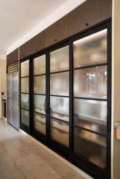 Black-framed sliding frosted glass doors conceal shelving and pantry storage. This Italian country villa kitchen was runner-up in the NKBA Supreme Kitchen Design award. Kitchen Pantry Design, Home Decor Kitchen, Kitchen Interior, Kitchen Designs, Country Kitchen, Kitchen Organization, Kitchen Ideas, Frosted Glass Door, Glass Doors